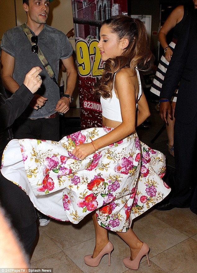 Twirl girl: Earlier, the dimpled teen queen wore a pink floral skirt and white crop-top for a signing of her debut album Yours Truly