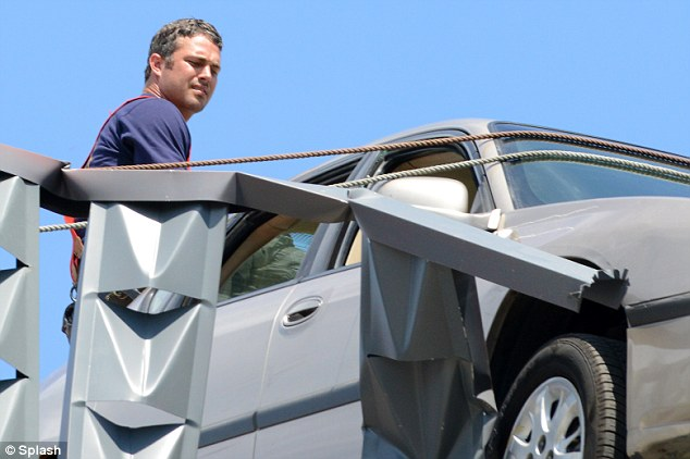 Action man: Taylor Kinney filmed a daring rescue ion the set of Chicago Fire in Chicago on Wednesday