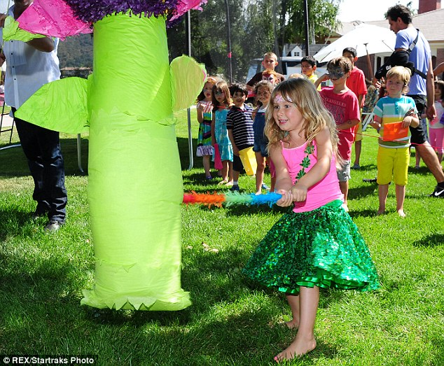 Doing her best: Stella gave it her all as she whacked the flower-shaped piñata