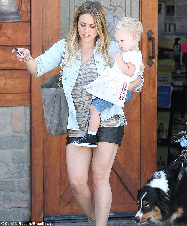 Mom, son and dog: Hilary held onto Luca while the family dog trailed behind