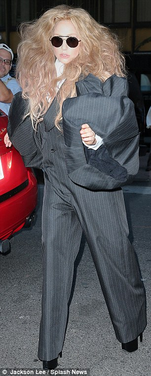 Defying gravity: The popstar teetered along in her towering black platform heels, which she wore with a bizarre grey pinstripe jumpsuit with huge voluminous sleeves and a white high-neck shirt