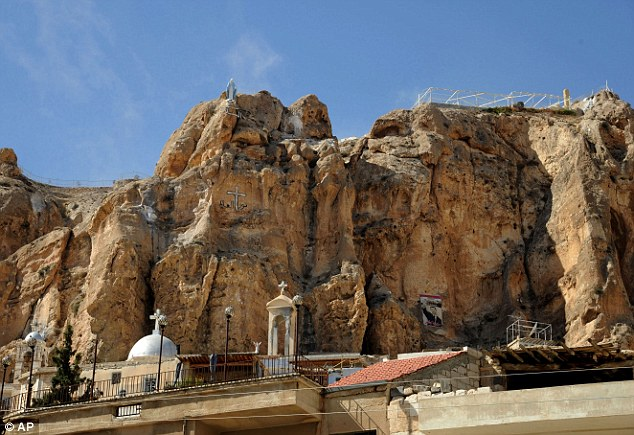 A church in Maaloula where fighting has been taking place overnight. A poster with the portrait of Syrian President Bashar Assad is seen bottom right
