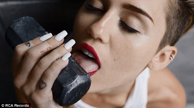 And this a metaphor for? At one point Miley licks a sledgehammer in the Terry Richardson inspired video, it's not clear as to which plot point this attends to