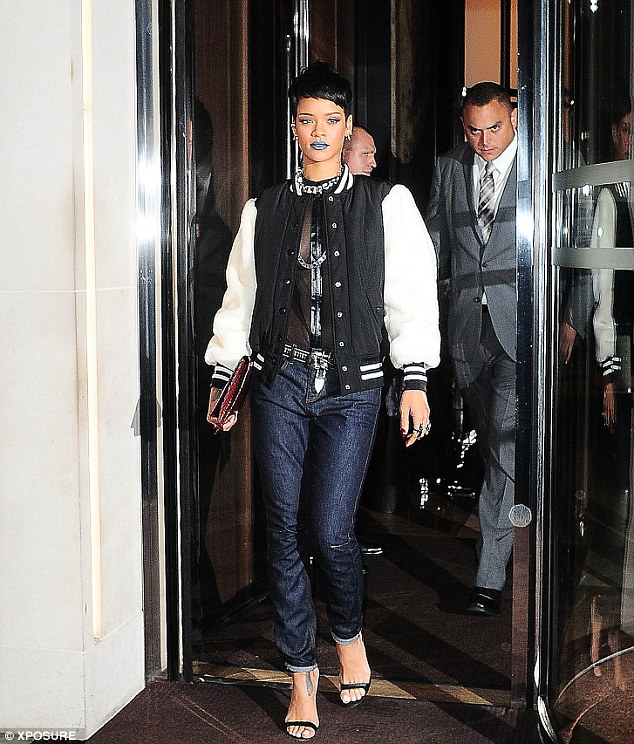 Androgynous: Rihanna paired a black and white varsity jacket with a see-through shirt and metallic blue jeans, with lots of chunky chains and jewellery