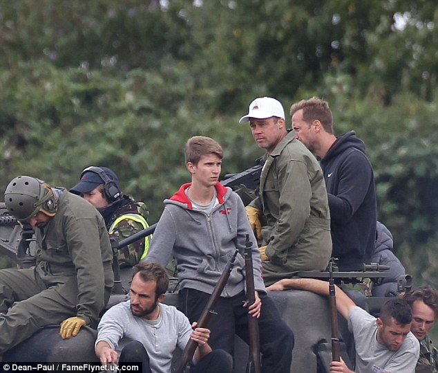 Hiding: Brad Pitt was rehearsing for his new film the Fury with extras in the British Countryside and wore a white baseball cap all day on set to hide his new haircut