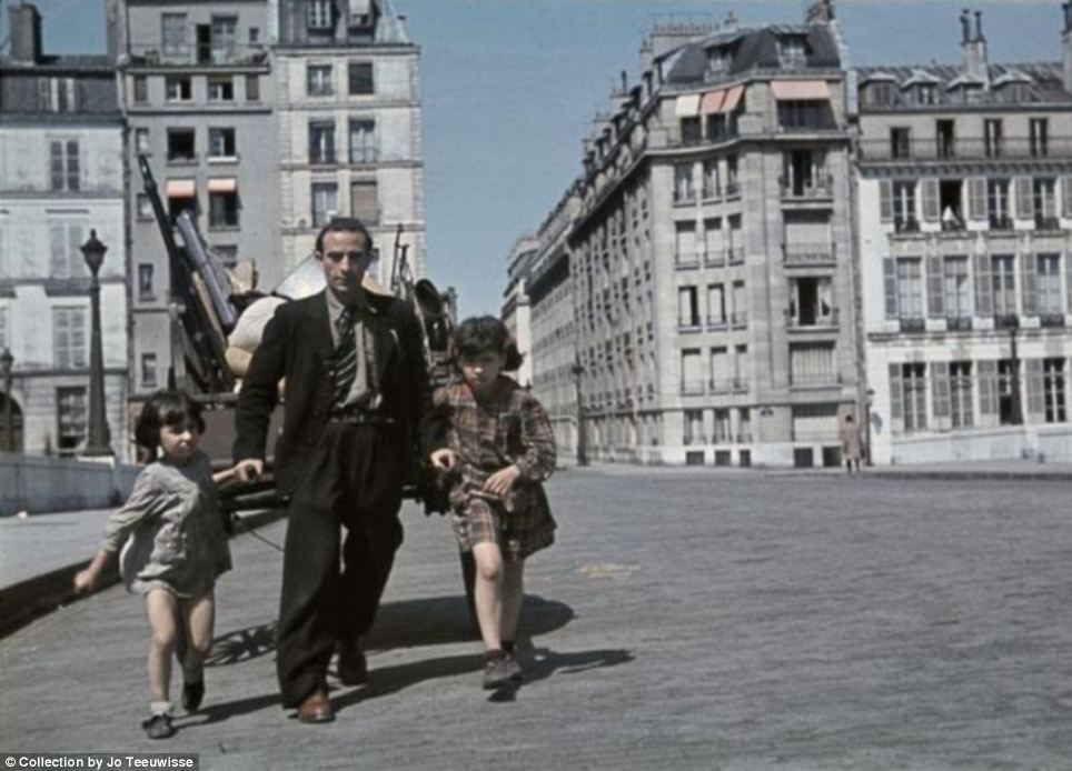 Running away? A harried looking man with two scruffily dressed girls drags a cart through the streets of Paris