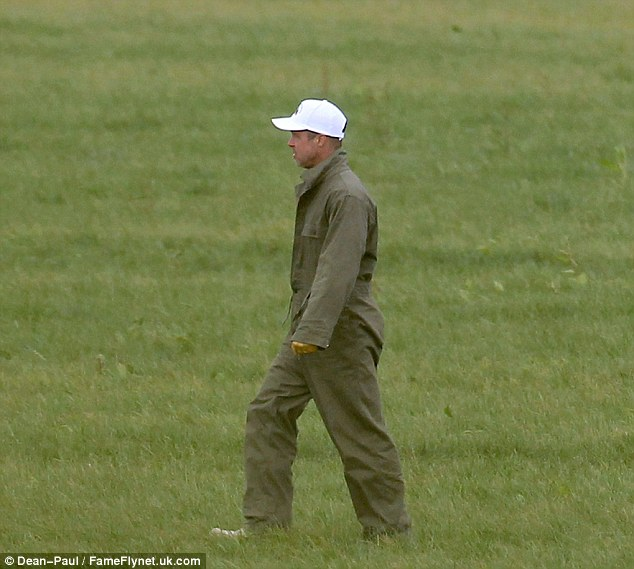 Walking in the wilderness: Brad was seen walking by himself across the grass fields - still wearing the baseball cap