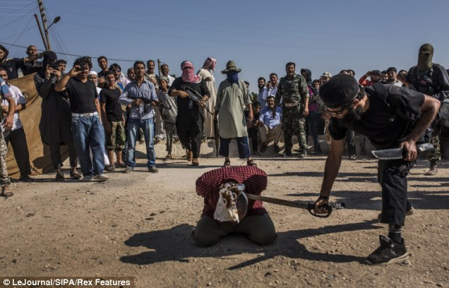 As a cheering crowd of fighters look on, an executioner - believed to belong to the Al Qaeda-linked faction ISIS - lines up his sword in a practice run before delivering the final blow