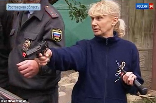 'Housewife' Inessa Tarverdiyeva demonstrates to police how she gunned down victims during a six year reign of terror that left 30 people dead