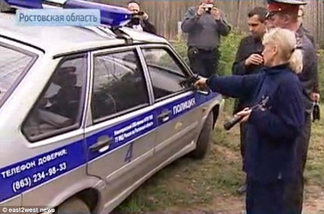 Inessa Tarverdiyeva shows how she shot one of her victims through a car window