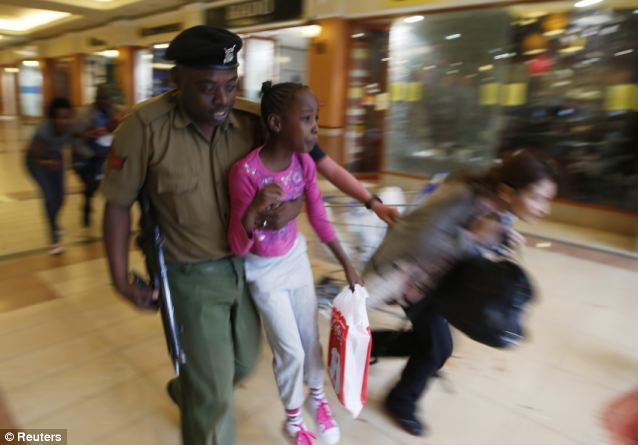 Children: A soldier carries one of the survivors to safety as armed police hunt for the gunmen