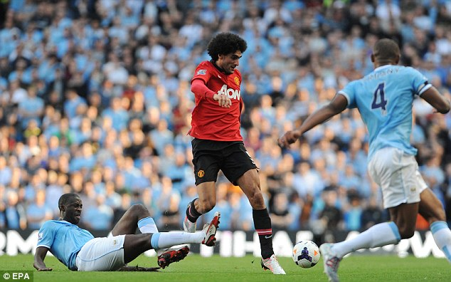 Crowded out: Marouane Fellain vies for the ball with Manchester City's Yaya Toure and Vincent Kompany