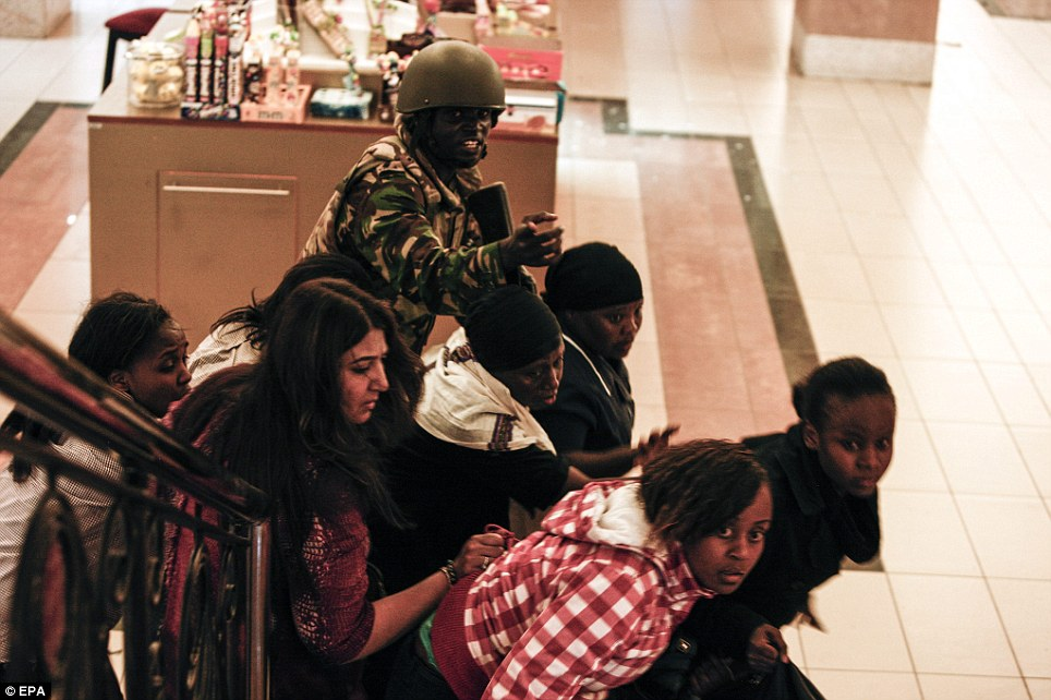 Shock: A soldier directs people up stairs inside the Westgate shopping mall after a shootout in Nairobi, Kenya. Gunmen had fired automatic weapons and grenades