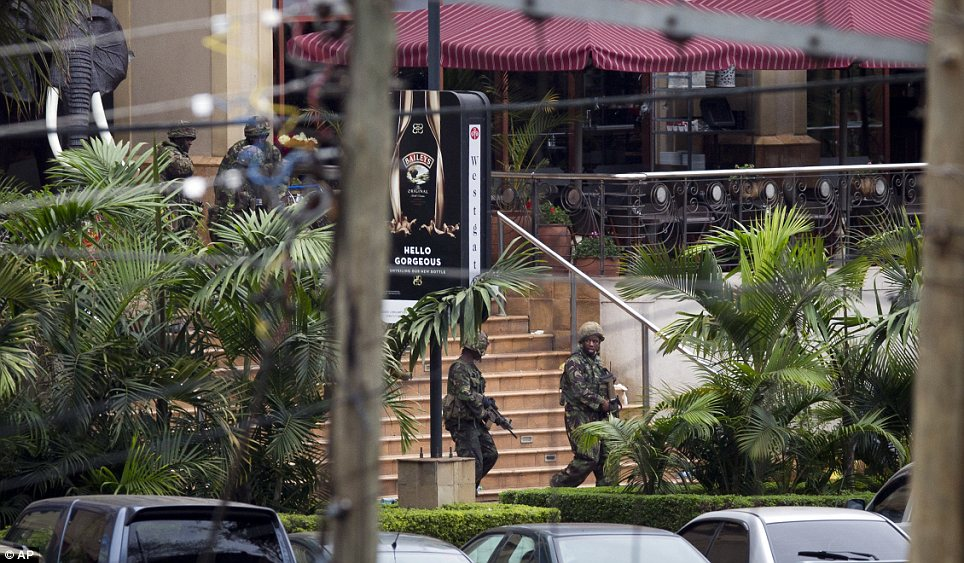 Tense: Soldiers from the Kenya Defense Forces walk out of the mall, following the sound of explosions and gunfire