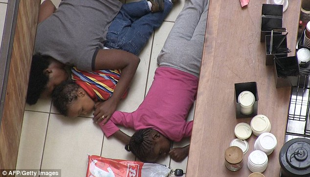 Two children and a woman hide behind a bar inside the shopping mall in the hope they won't be found by the gunmen