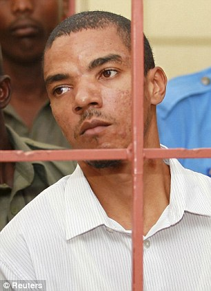Jermaine John Grant (C, in white), a British citizen, is guarded by Kenyan police in court in Shanzu