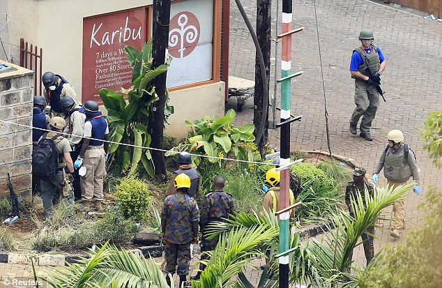 Gathering evidence: Foreign forensic experts, flanked by Kenyan military personnel, check the perimeter walls around Westgate shopping centre