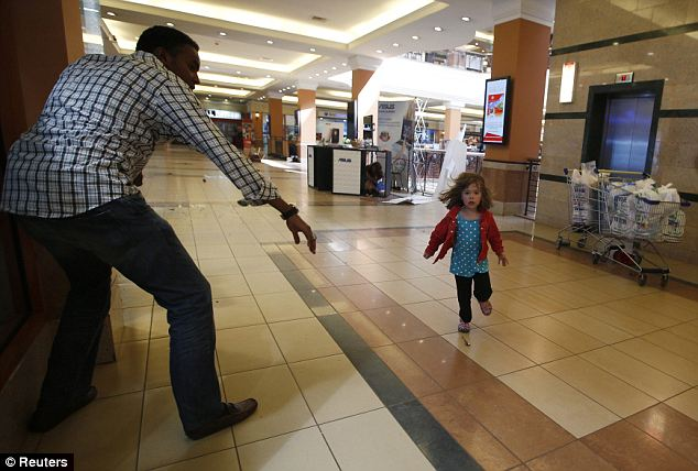 Their story: Portia Walton runs for the safety of Kenya mall hero Abdul Haji. The Waltons have now shared their harrowing tale, giving backstory to this now-iconic photo