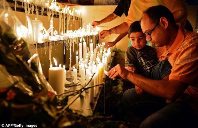 Prayer: A father lights candles with his son during the 24-hour vigil