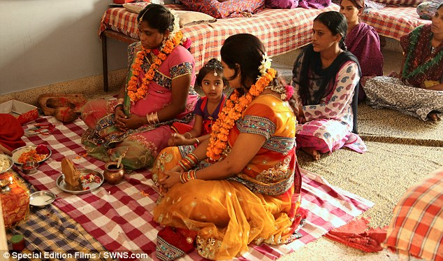 Two heavily pregnant surrogate mothers undergo a 'blessing' inside the house by a hindu priest before they give birth. They ware paid $8,000 each per child