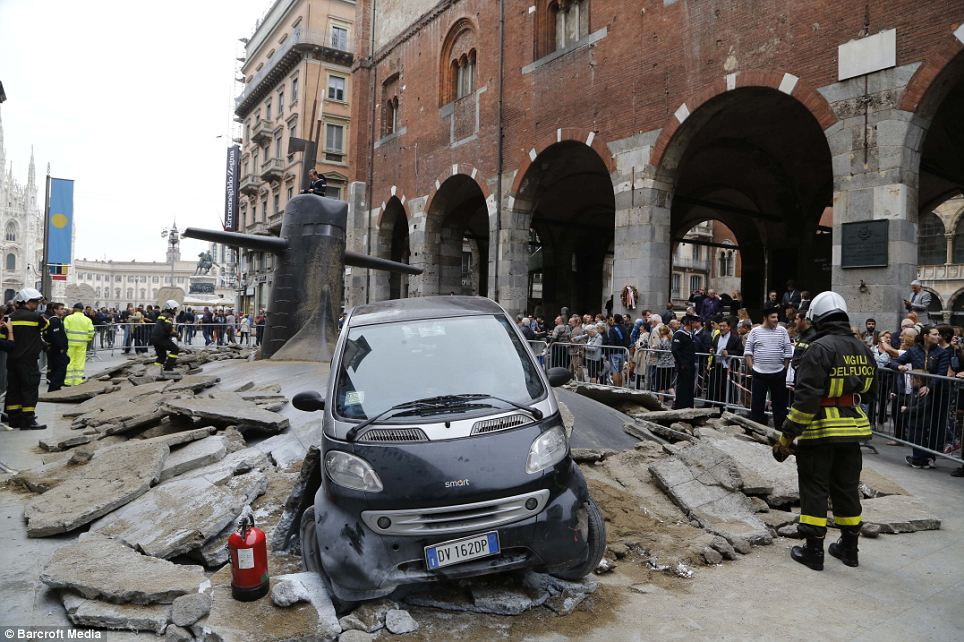 A little lost? A submarine appears to have surfaced from beneath a street in Milan in this scene which locals discovered as they got up for work yesterday morning