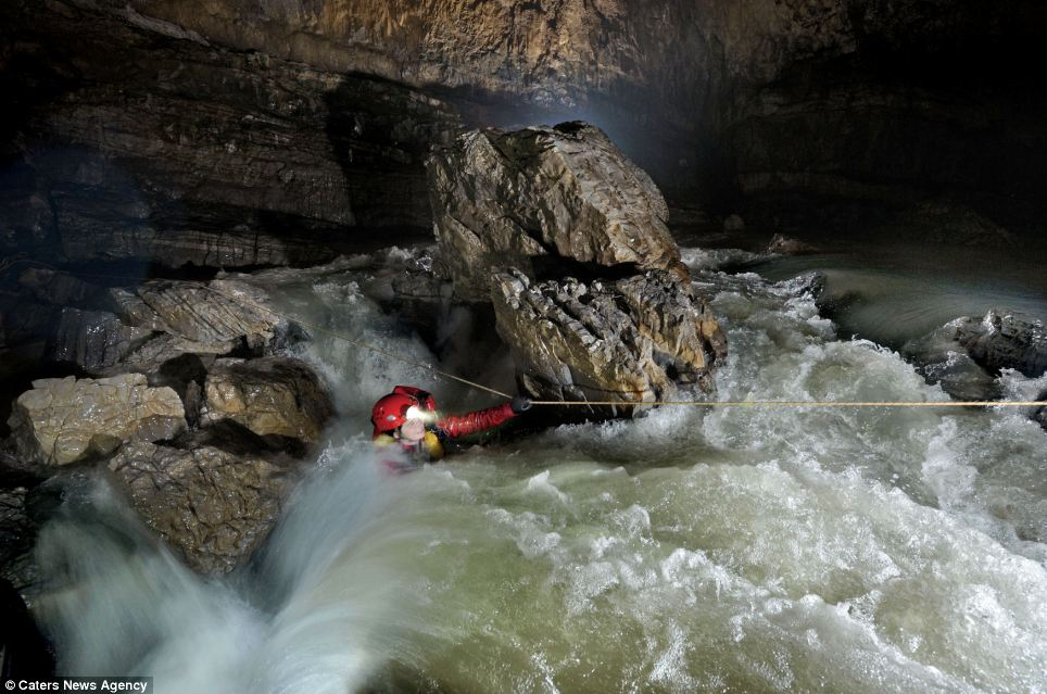 American speleologist Erin Lynch struggles to pull her way across a raging torrent of white water, which is the main river in Quankou Dong