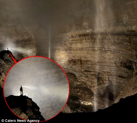 A caver stands on the central ridge overlooking the cathedral-like Cloud Ladder Hall, towering up into the fog