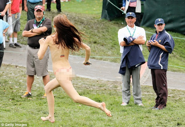 Hey! A streaker runs past U.S. Team Captain Fred Couples on the18th hole during the Day Four Singles Matches at the Muirfield Village Golf Club on October 6, 2013 in Dublin, Ohio