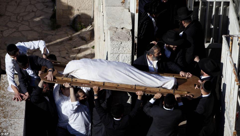 Enveloppé dans un linge et attaché à une planche de bois, le rabbin Ovadia Yosef est pris en charge par les personnes qu'il a dirigé pendant des décennies