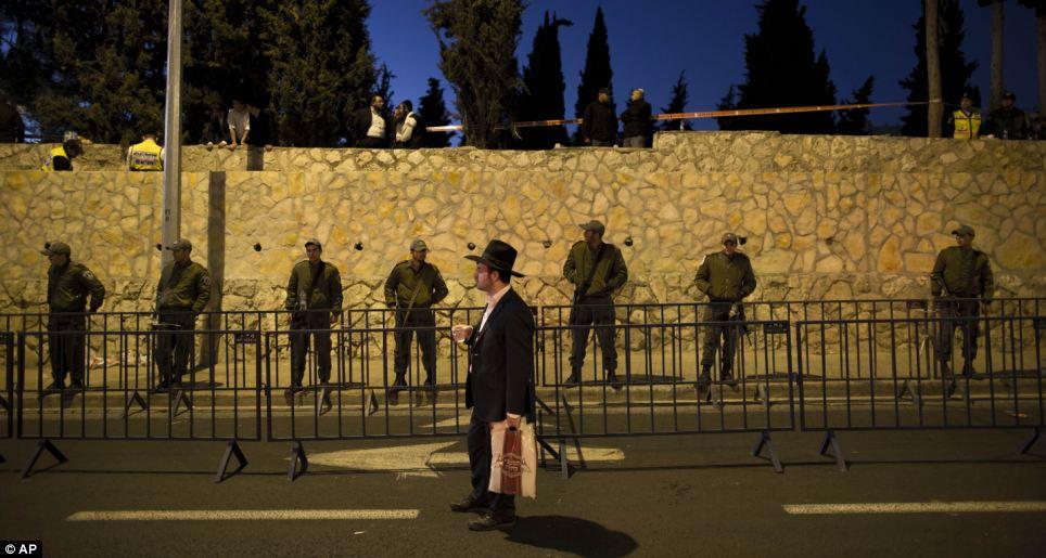 Les agents de la police des frontières israéliennes sécuriser le périmètre cimetière.  Comme les fondus de commotion, un disciple se tient soigneusement reflétant