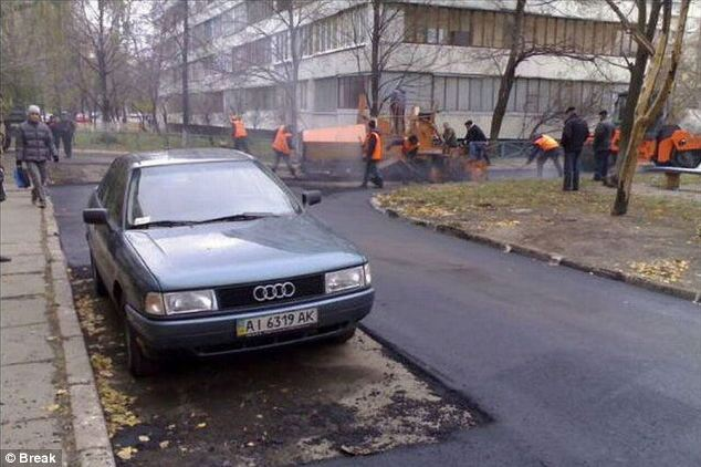 In a rush? Workers resurface the road around this parked Audi