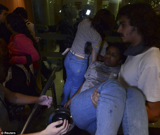 Injured: Demonstrators help the staff of a McDonald's store during the clash between anti-government demonstrators and riot police