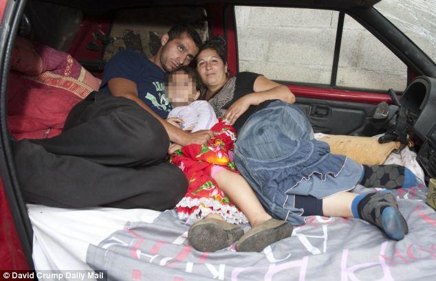 Cramped: Rostas miembros de la familia, Victor, 25, con la esposa Angele, 25, con su hija en el coche abandonado duermen y viven en