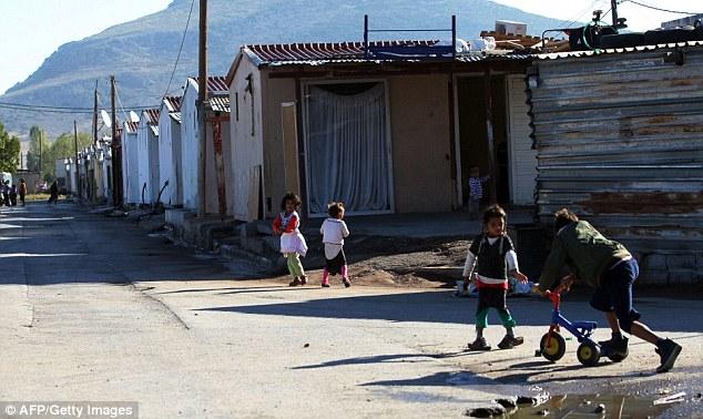 Parque infantil: los niños romaníes que se divierten en el campamento en el campamento con hierro corrugado para el techo de muchos de los edificios