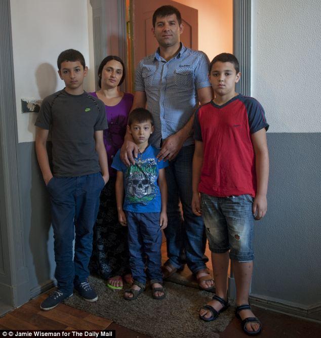 Catalin Feraru fotografiado junto a su familia en el bloque de apartamentos donde él y docenas de otras familias Ronamy viven.  Fotografiado con él están su esposa Crenguta, el más joven hijo Alex (cinco), el más viejo hijo Derek (11), y medios hijo Elisei, en rojo (nueve)