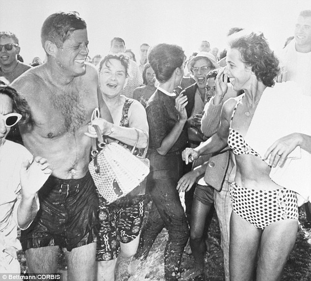 Beach boy: JFK in 1962, surrounded by admirers after a swim at Santa Monica