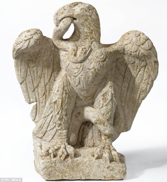 The sculpture features an eagle grasping a writhing serpent