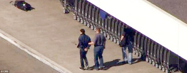 A man is led away from Los Angeles International Airport in handcuffs on Friday. It is unknown whether he is related to the shooting