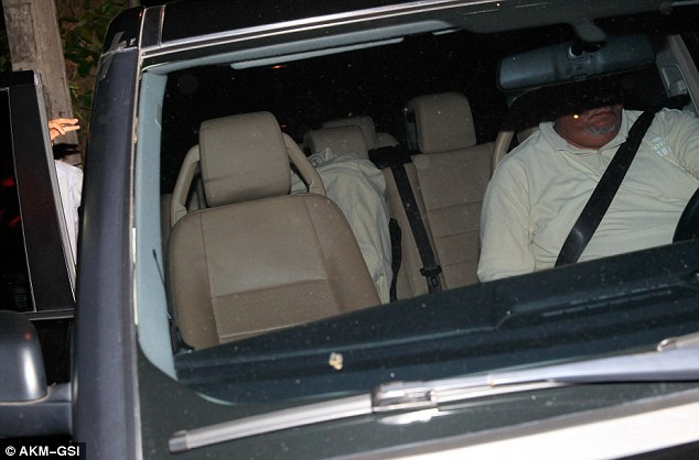 Disappearing act: Justin is seen under a bedsheet as he gets into an awaiting SUV