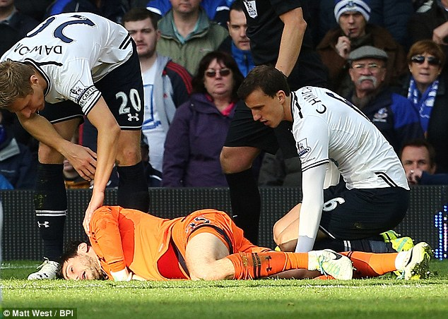 Concussed: A knocked out Hugo Lloris lies on the ground after a challenge from Romelu Lukaku