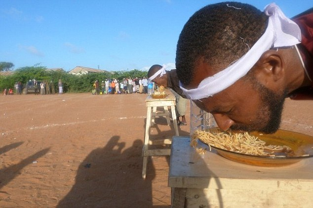 A man whose hands have been tied behind his back takes part in an eating competition during the games