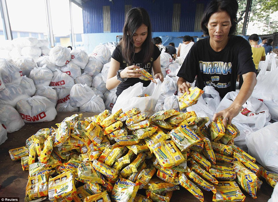Aid effort: Volunteers pack relief goods inside a Department of Social Welfare and Development warehouse before shipping out to devastated provinces