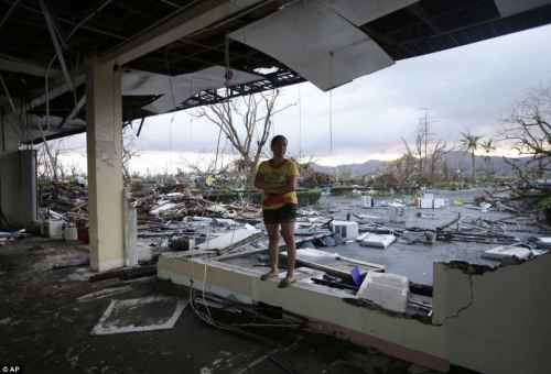Shock: A woman stands amidst the devastation. Flood water can be seen in the background covering most of the area around the demolished building