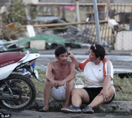 Residents sit outside their damaged house