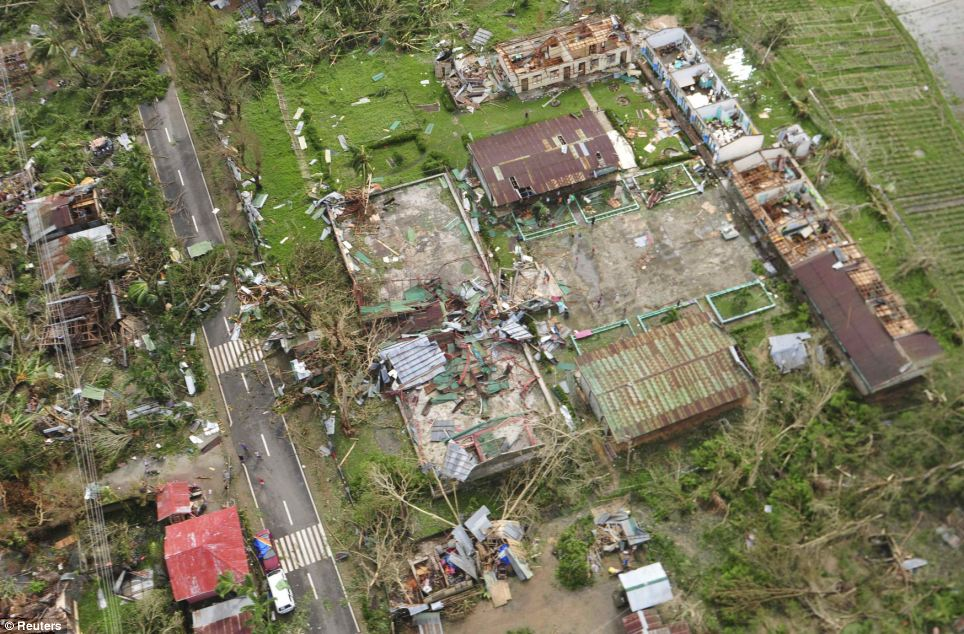 From above: An aerial view shows badly damaged houses, including many without a roof, and blocked roads in the Philippine province of Iloilo