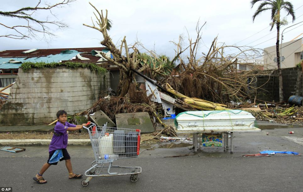 Scavenging: A young boy pushing a trolley in search of water passes a coffin containing a victim of Typhoon Haiyan in Tacloban