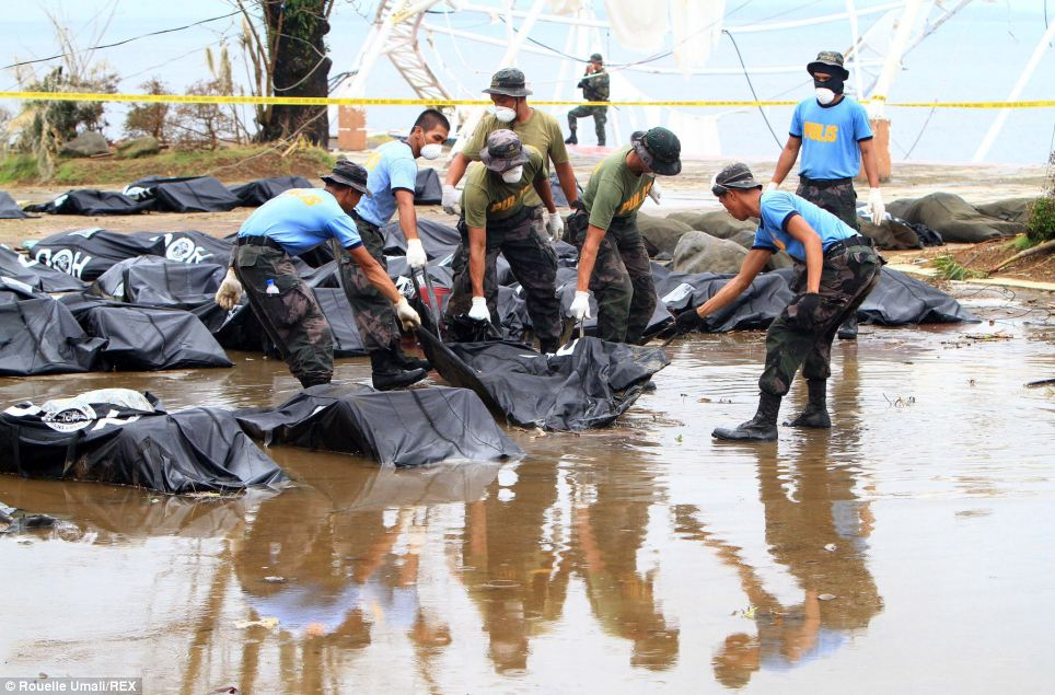Dreadful task: Soldiers pull bags filled with typhoon victims from the floor waters and leave them on higher ground