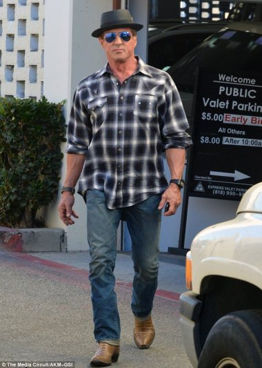 Action man: Stallone showed he hasn't let age get in the way of a tough exercise regime, showing off his massive arms in a black-and-white plaid shirt