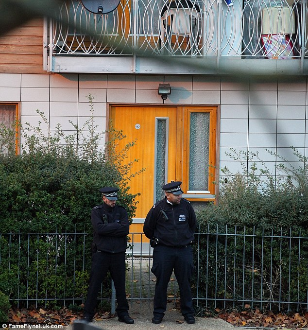 Investigation: Police stand guard at the property in Brixton, south London, and are following many lines of inquiry including links to 13 addresses across London