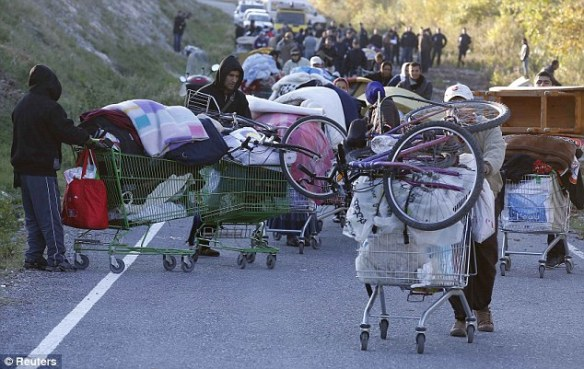 Eviction: Roma families pictured carrying their belongings down the road after being evicted by French police from their illegal camp near the Var river in Nice, southeastern France